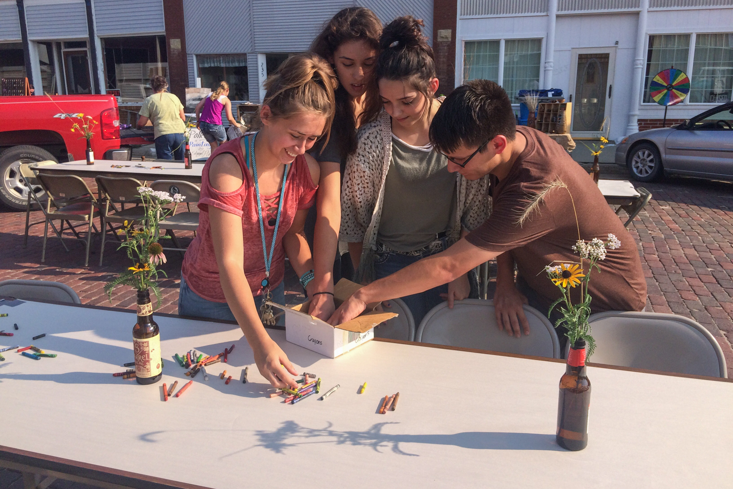 Students help set tables along Main Street with native flowers. Tables covered with paper and crayons invite visitors to sit and doodle.